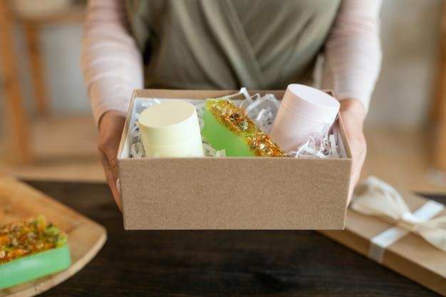 Mains de jeune femme emballant des barres de savon naturel frais fait à la main dans une boîte en carton tout en préparant des cadeaux pour ses amis avant les vacances