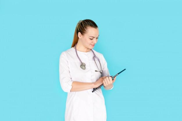 Mains de jeune femme médecin en uniforme blanc avec phonendoscope sur son cou, tenue de dossier noir