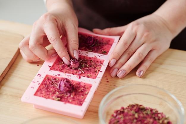 Mains de jeune femme mettant de petits boutons de rose sur le dessus de barres de savon rose dans des moules en silicone tout en terminant le travail créatif