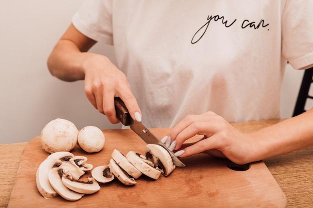 Les mains d'une jeune femme ont coupé des champignons avec un couteau sur une planche à découper dans la cuisine