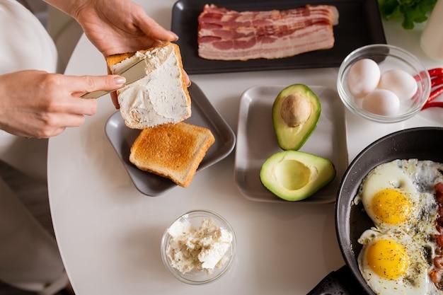 Mains de jeune femme à tartiner du beurre ou du fromage sur des toasts rôtis tout en allant avoir des œufs au plat avec de l'avocat et des sandwichs