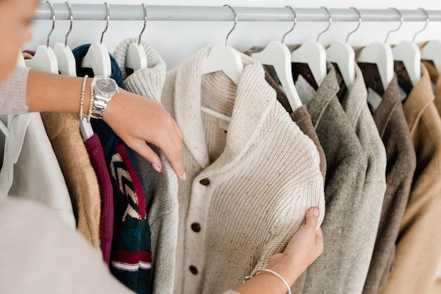 Mains de jeune femme tenant un cardigan tricoté blanc tout en choisissant de nouveaux vêtements dans une boutique moderne