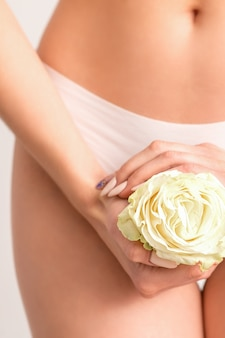 Les mains de la jeune femme tenant une fleur blanche couvrant la zone de bikini épilée isolée sur fond de studio blanc.