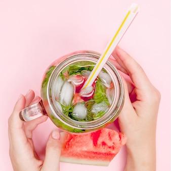 Mains de jeune femme tenant de la limonade d'agrumes fraîchement pressée.