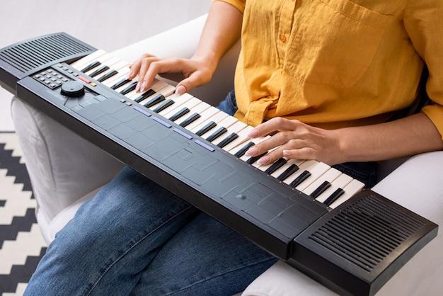 Mains de jeune femme en tenue décontractée assise sur un fauteuil en cuir blanc dans le salon et en appuyant sur les touches du clavier du synthétiseur musical