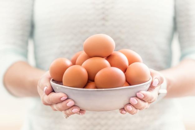 Les mains d'une jeune femme tiennent un bol d'œufs de poule.