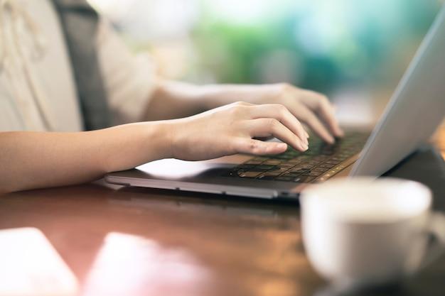 Mains de jeune femme utilisant un ordinateur portable dans un espace calme