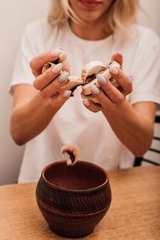 Mains d'une jeune femme versant des champignons hachés dans une casserole dans la cuisine