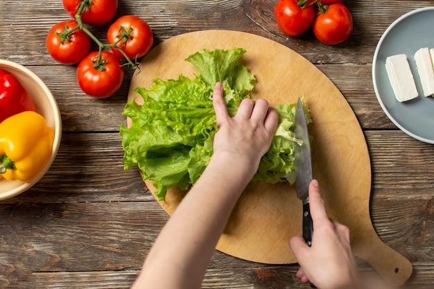 Mains de la jeune fille, couper la laitue sur une table