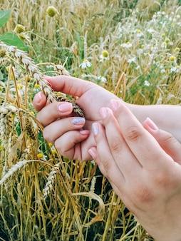 Les mains de la jeune fille sur le fond d'un champ de blé