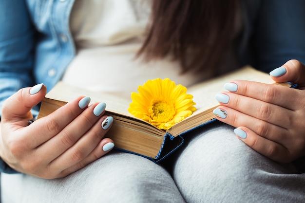 Les mains de la jeune fille sur un livre avec une fleur jaune