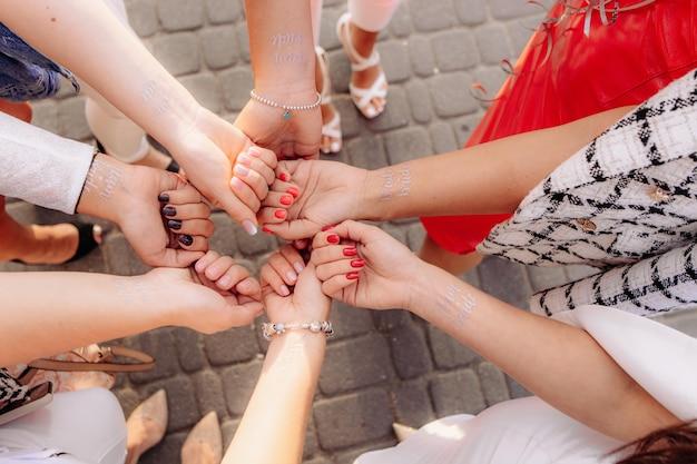 Les mains de la jeune fille avec un tatouage temporaire de l'équipe de la mariée. le concept d'une partie de bachelorette.