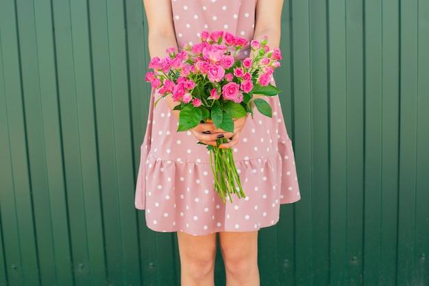 Mains de la jeune fille tenant un beau bouquet de roses roses