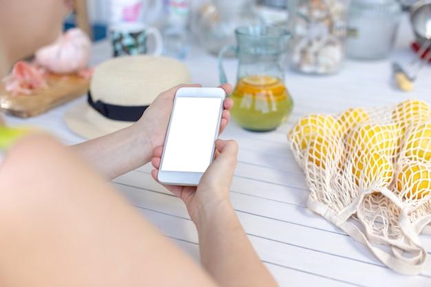 Mains d'une jeune fille tenant un smartphone blanc, sur une table en bois blanche, à côté de citrons jaunes dans un sac