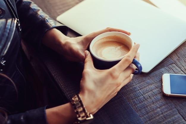 Mains de la jeune fille tenant une tasse de café