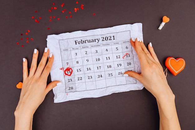 Les mains de la jeune fille tiennent un calendrier avec le 14 février encerclé. vue de dessus. la saint-valentin. un cercle de bonbons des coeurs de kars. fond gris