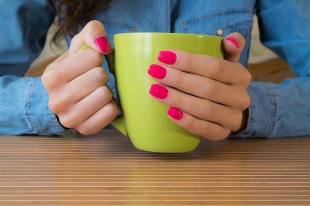 Mains d'une jeune fille avec un vernis à ongles rouge tenant une grande tasse verte