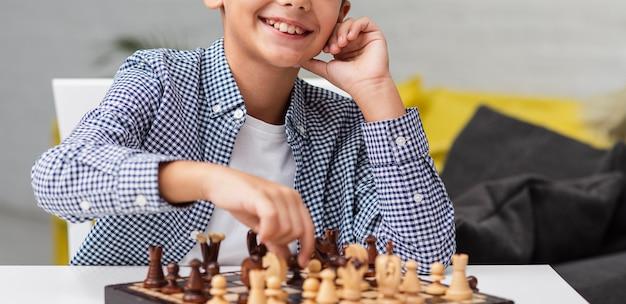 Mains de jeune garçon jouant aux échecs