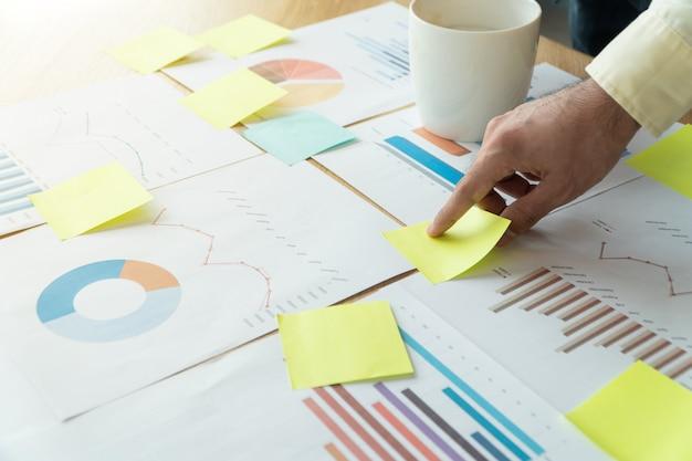 Les mains d'un jeune homme d'affaires sont des notes coincées dans un document.