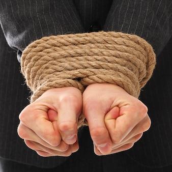 Les mains d'un jeune homme attaché avec une corde