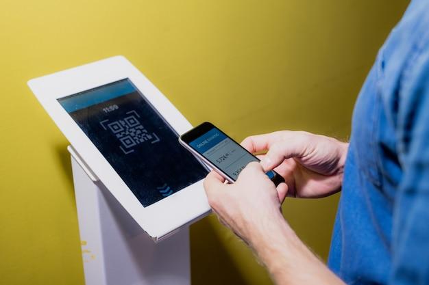 Mains de jeune homme contemporain avec smartphone debout par terminal tout en allant acheter des billets pour un film au cinéma
