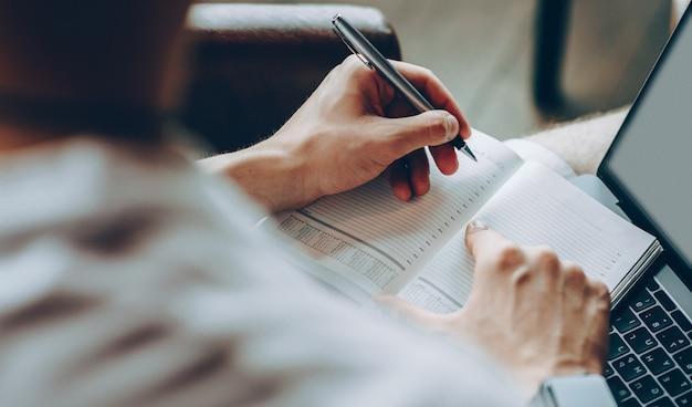 Mains d'un jeune homme écrivant dans un cahier