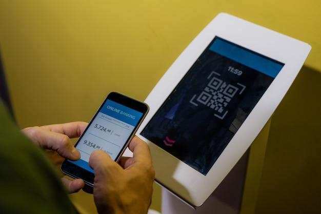 Mains de jeune homme mobile tenant le smartphone sur l'affichage du terminal tout en allant acheter des billets pour un film au cinéma