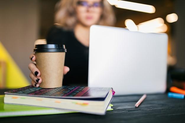 Mains de jeune jolie femme assise à table en chemise noire travaillant sur ordinateur portable au bureau de co-working