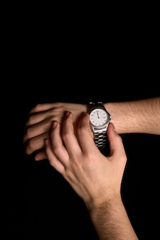 Mains d'une jeune personne regardant une horloge sur le point de marquer la première seconde de la nouvelle année 2019