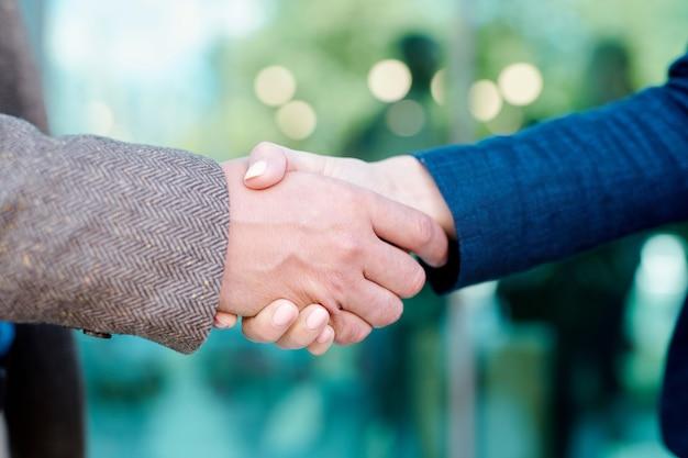 Mains de jeunes employés contemporains en poignée de main symbolisant le partenariat, la confiance et l'unité