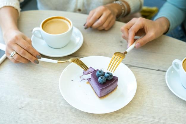 Mains de jeunes femmes amicales avec des fourchettes prenant morceau de gâteau aux myrtilles appétissant sur une assiette pour profiter de son goût