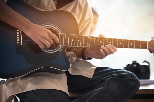Mains jeunes gens que le guitariste joue pour le spectacle en direct dans la salle de classe de musique à l'université