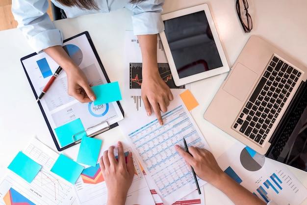 Mains de jeunes hommes d'affaires pointant au rapport de graphique d'affaires sur tablette au bureau