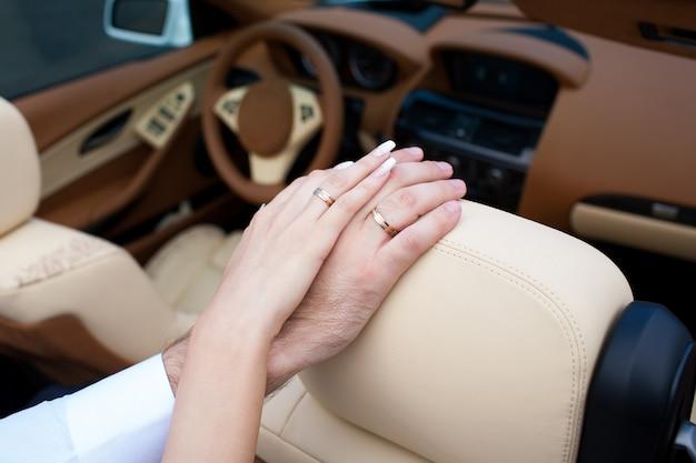 Les mains des jeunes mariés avec des alliances se bouchent