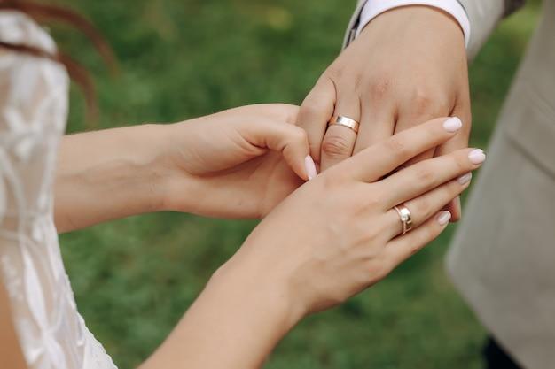 Mains de jeunes mariés avec des anneaux de mariage et un bouquet de mariage. les jeunes mariés avec des anneaux de mariage et un