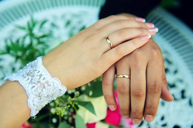 Mains de jeunes mariés, bouquet de mariée. anneaux de mariage en or sur le doigt de la mariée et le marié, gros plan. concept d'une célébration de mariage.