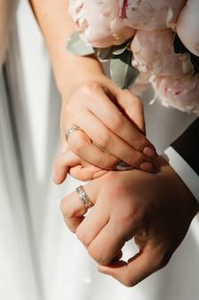 Les mains des jeunes mariés qui portent une alliance