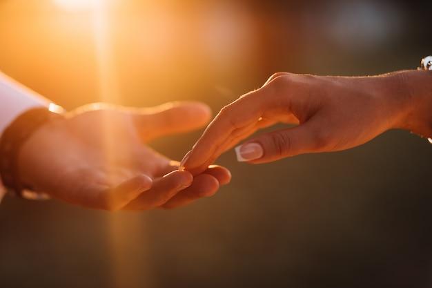 Les mains des jeunes mariés se touchent affectueusement