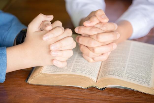 Les mains jointes en prière sur une sainte bible dans le concept d'église pour la foi, la spiritualité et la religion, femme priant sur la sainte bible le matin. main de femme avec la prière de la bible.