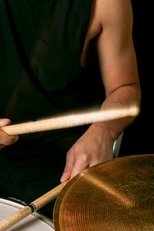 Mains jouant de la batterie avec des bâtons