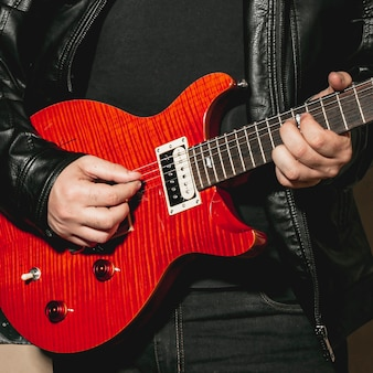Mains jouant de la belle guitare rouge