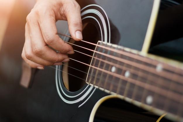 Mains jouant de la guitare acoustique.