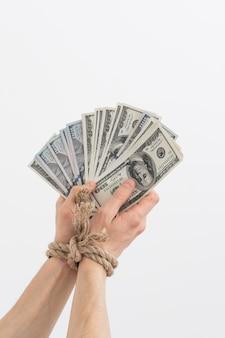 Les mains liées tiennent la dépendance de l'argent sur le crédit hypothécaire