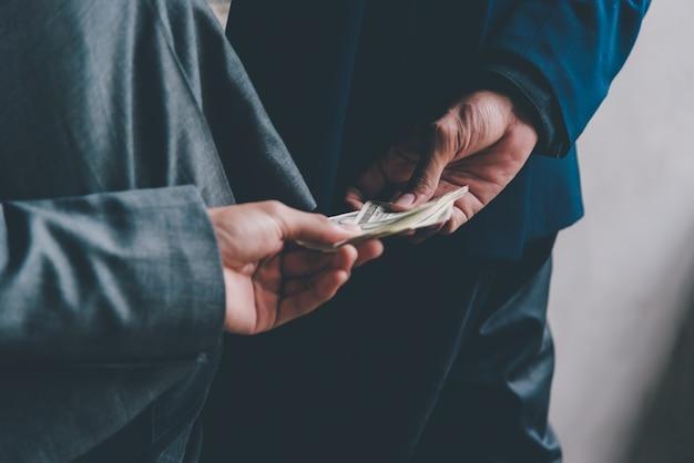 Les mains livrent l'argent du pot-de-vin à d'autres en trompant les hommes d'affaires pour corruption sur des dommages à l'ex