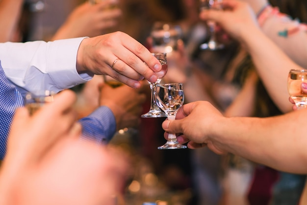Mains avec des lunettes de vodka célébrant la fête traditionnelle russe