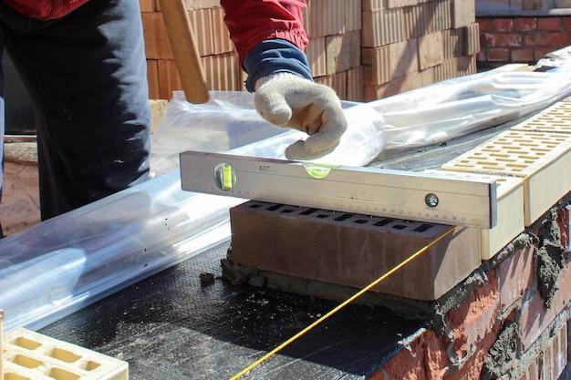 Les mains des maçons avec une truelle de maçonnerie pour la maçonnerie du nouveau mur de la maison sur les fondations. gros plan sur un maçon industriel installant des briques. maçon et maçon travaillant avec des briques et des murs de construction.