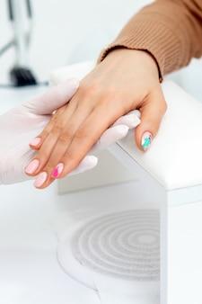 Mains de maître de manucure pulvérisant des ongles