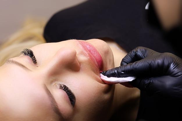 Les mains d'un maître tatoueur qui efface l'excès de pigment des lèvres du modèle avec une éponge en coton