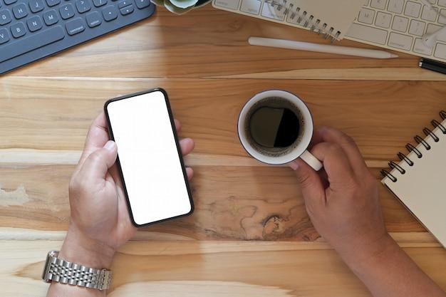 Mains mâles à l'aide de la maquette d'écran vide smartphone au bureau