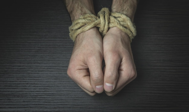 Mains mâles attachés avec une corde